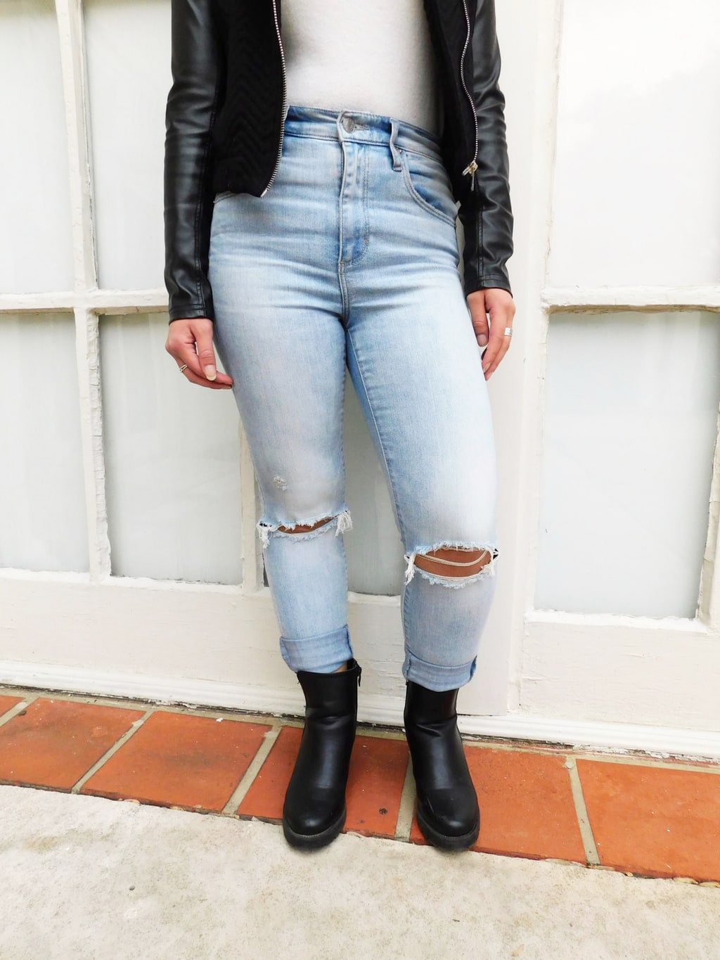 Fashion at Jefferson University: Jackie wears high-waisted, light-wash denim jeans with a white turtleneck tucked in. These jeans have distressed knees and are worn cuffed.