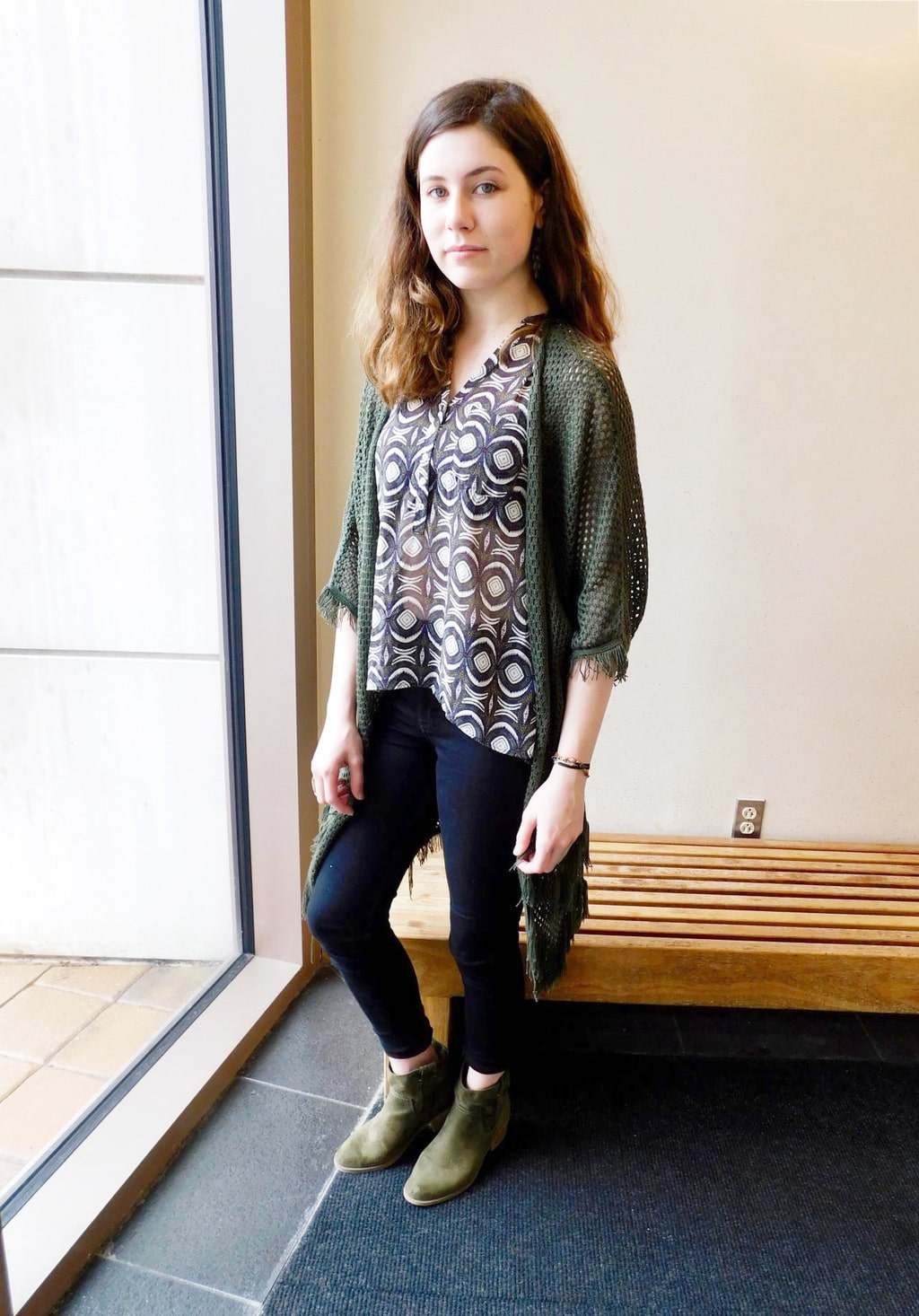 Jefferson University student Jenna sports a silky see-through black button-up blouse with a white pattern, black fitted skinny jeans, and a casual loose-knit olive green cardigan.
