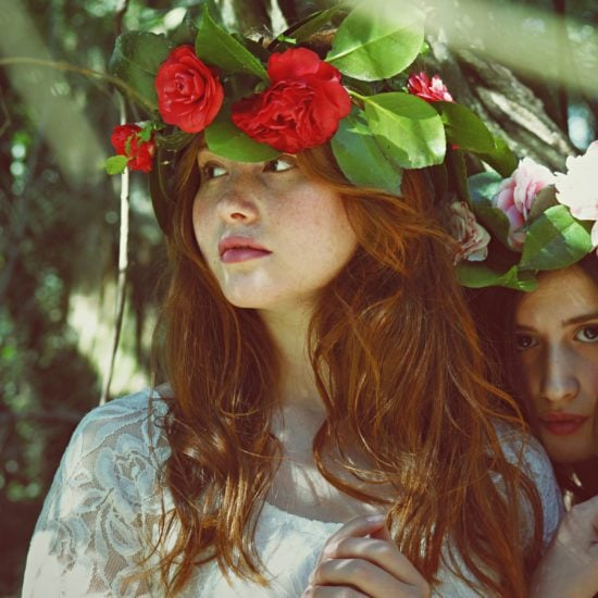Two women wearing flower crowns