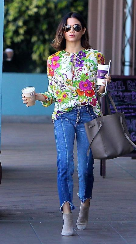 Jenna Dewan wearing dark aviator sunglasses, a floral tie-neck blouse, gray tote bag, side seam jeans, and taupe ankle booties