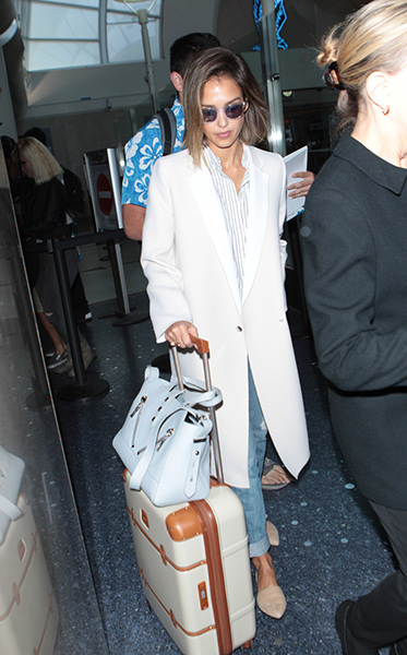 Jessica Alba in boyfriend jeans, a white coat, a striped top, and nude flats