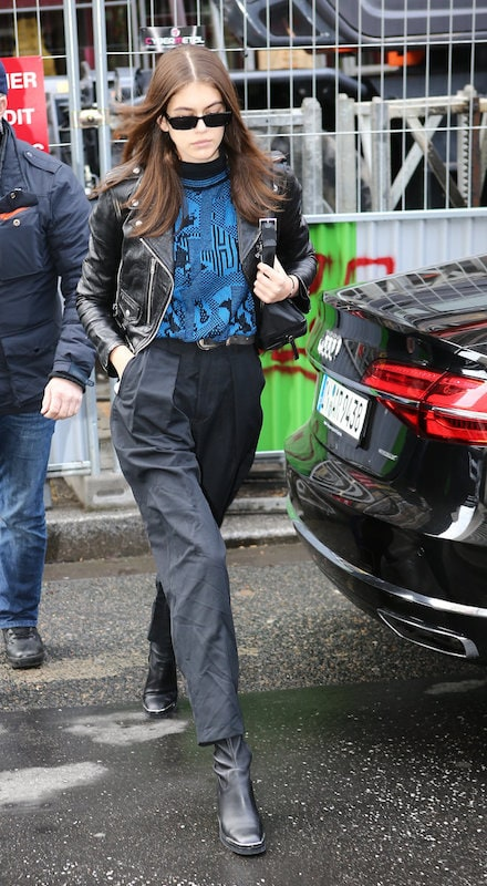 Kaia Gerber wearing a blue and black geometric print sweater, a black leather moto jacket, black square sunglasses, black pleated trousers, and black mid-calf booties