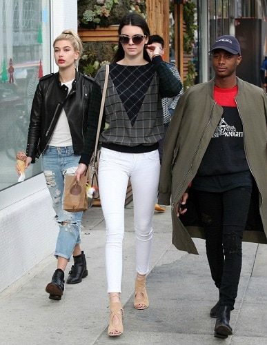 Kendall Jenner wearing a graphic print sweater and white skinnies