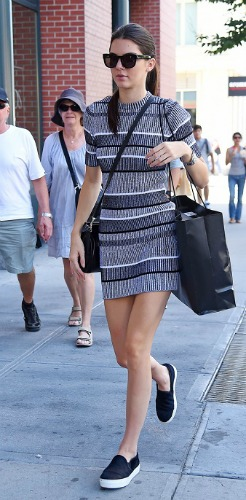 Kendall Jenner wearing a striped dress and slip on sneakers