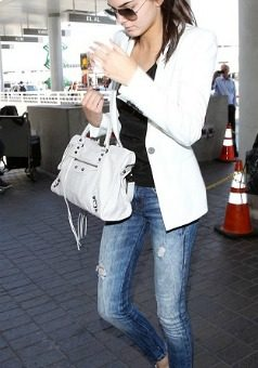 Kendall Jenner wearing a white blazer, jeans, and metallic shoes