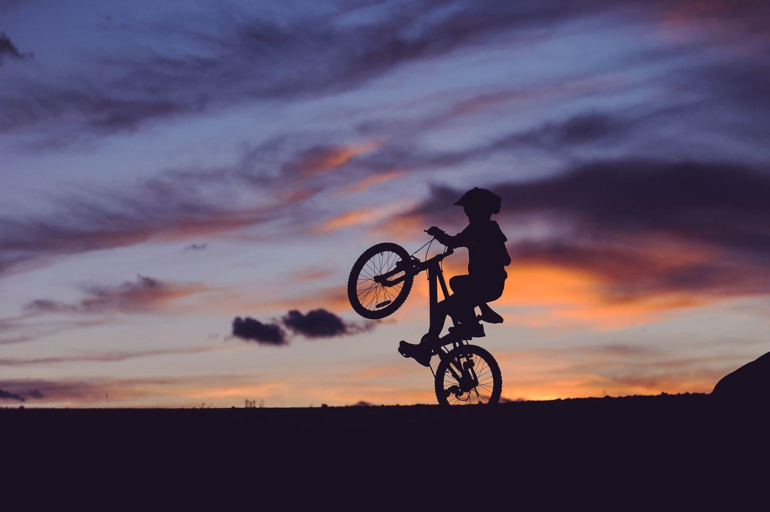 kid on bike with sunset
