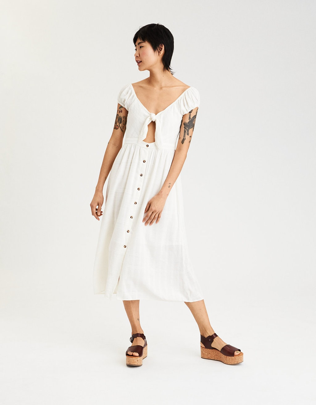 Photo of a model wearing a white knot front midi dress.
