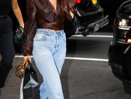 Kourtney Kardashian wearing a slouchy ribbed black sweater, small black sunglasses, olive green shiny leather pants, black lace-up combat boots, and a black mini backpack