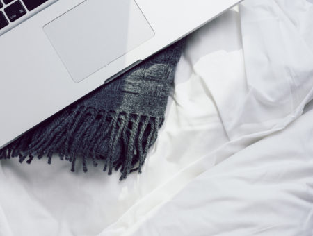 Laptop on a bed - self care lessons from chronic illness