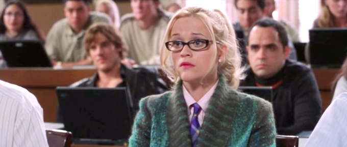 Elle Woods in class at Harvard in the movie Legally Blonde, wearing a pink button-down shirt, green fur jacket, glasses, and a purple tie