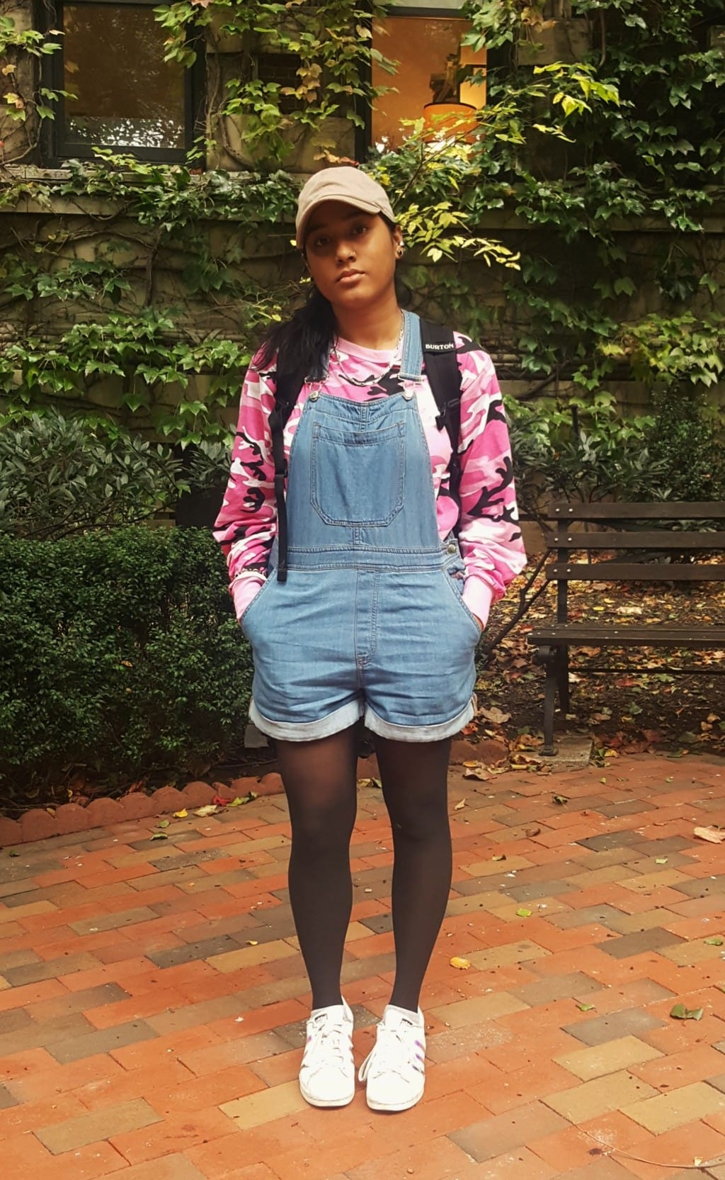 Barnard College student Alema wears a casual set of overall shorts with a bright pink camouflage long-sleeve tee underneath. She tops off her look with a tan baseball cap and black tights.
