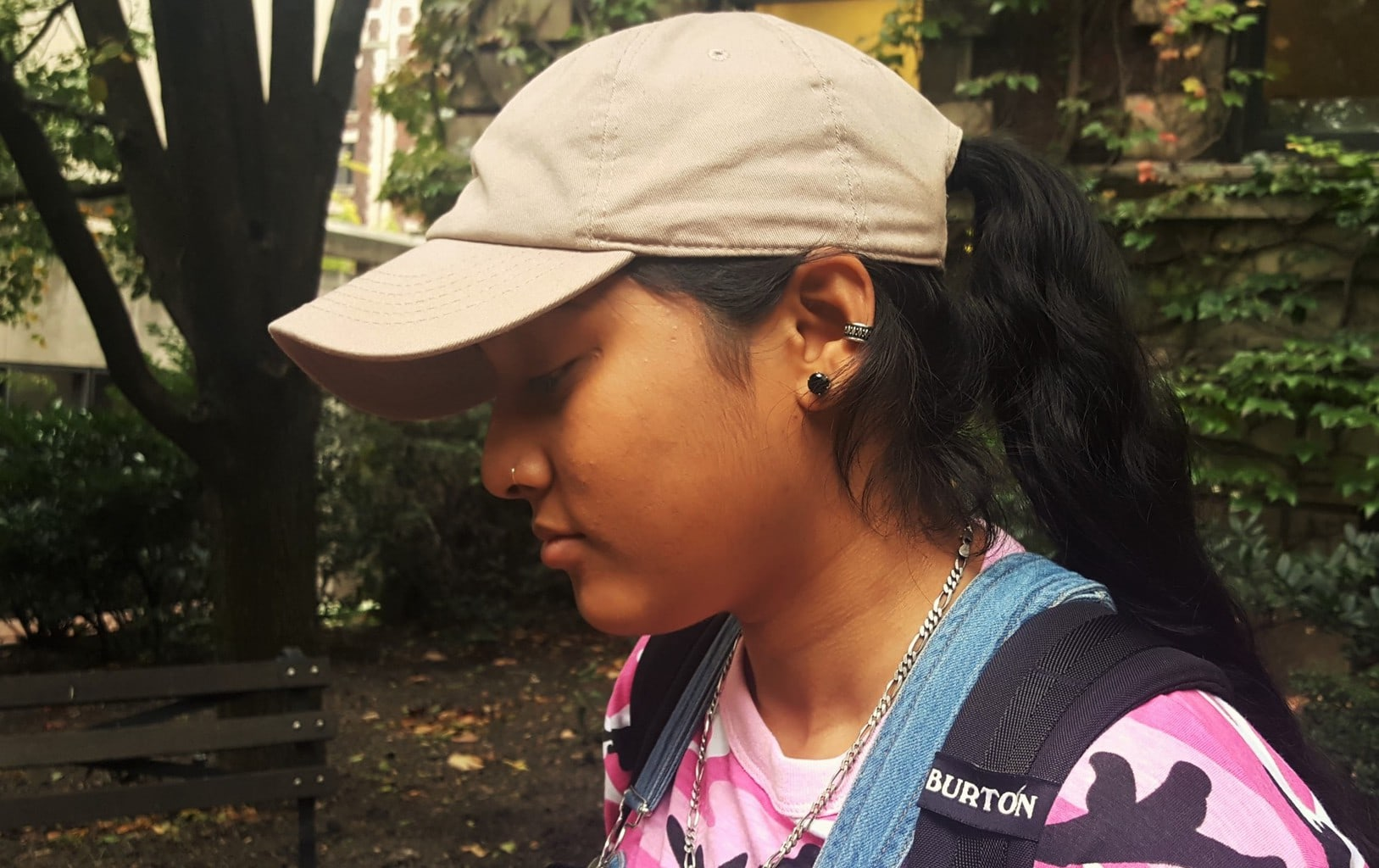 Alema wears a tan baseball cap with her black stud earrings and cartilage piercing.