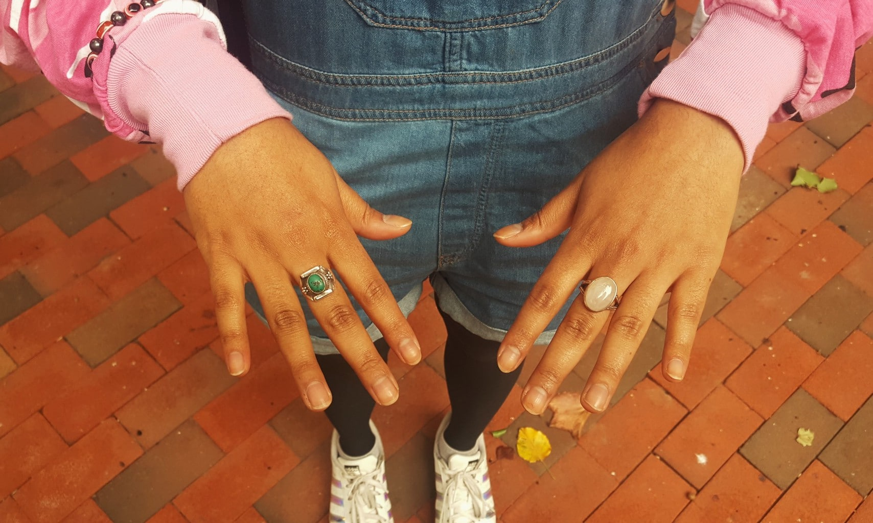 Barnard College student Alema sports mismatched accessories with a pink windbreaker jacket. Her oval opal ring and bright green vintage silver ring compliment her overall shorts.