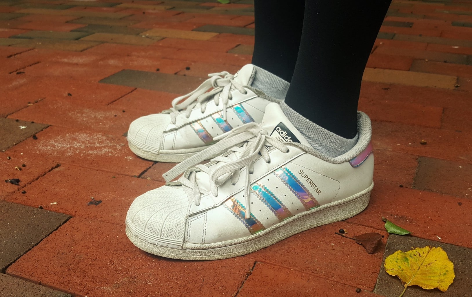 Alema's vintage-style white Adidas have holographic panels and rubber toes.