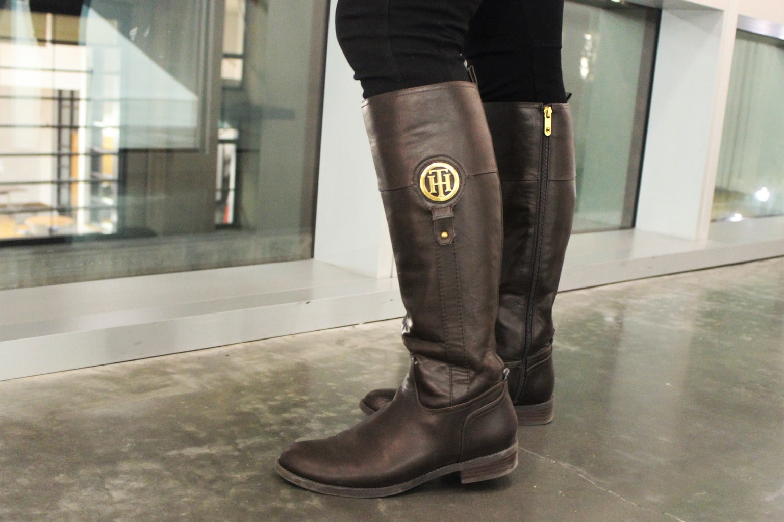 Catherine wears tall flat brown riding boots with gold accents.