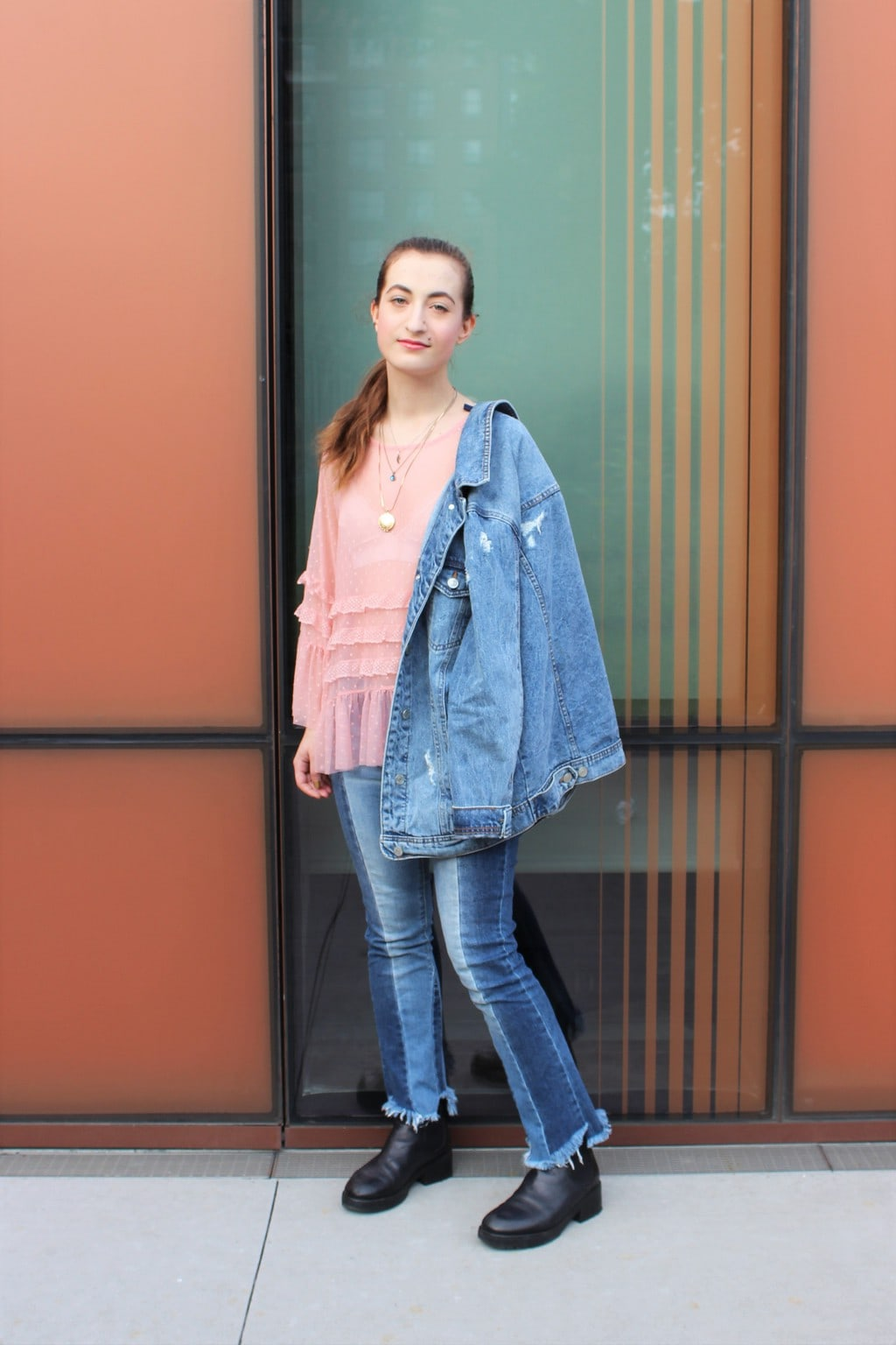 Barnard College at Columbia University student Francesca wears the perfect denim on denim outfit with a ruffled, sheer pink blouse with a white lace bralette underneath, patchwork raw-edge denim jeans, and an oversized light-wash denim jacket.