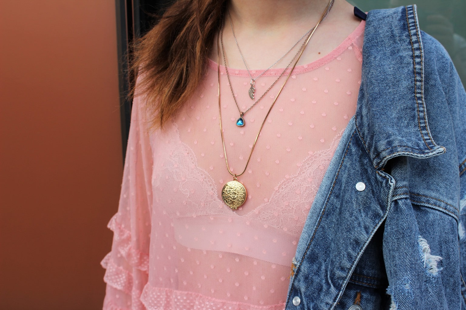 Barnard College student Francesca accessories her sheer, silky pink blouse with layered gold necklaces and a denim jacket.