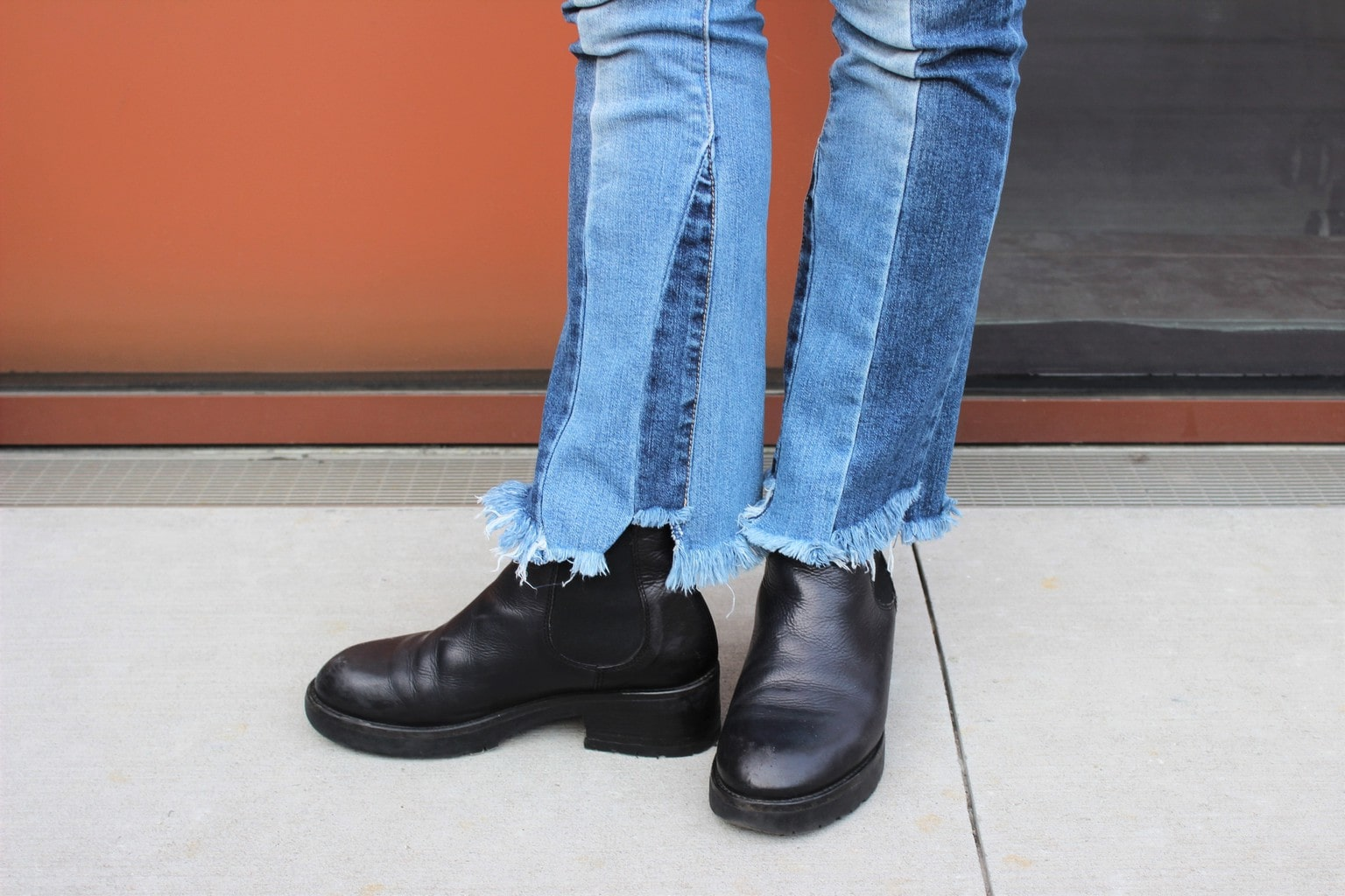 Raw-edge patchwork denim jeans with chunky black boots.