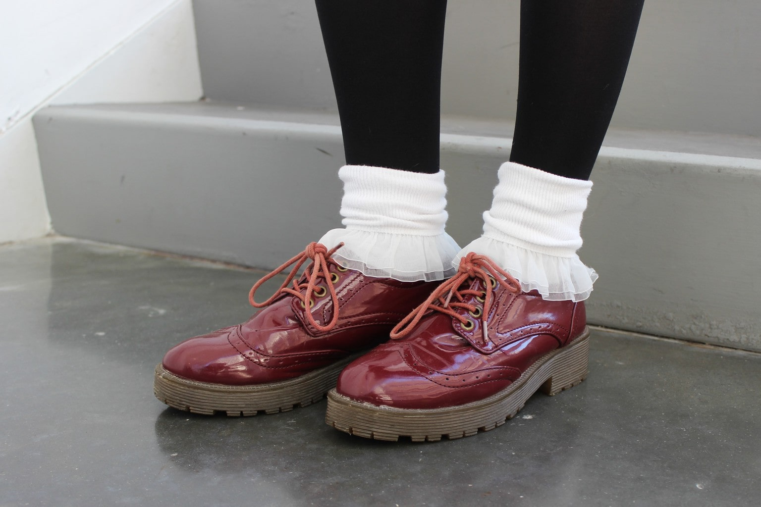 Hannah pairs white ruffled socks with chunky burgundy lace-up Doc Marten loafers.