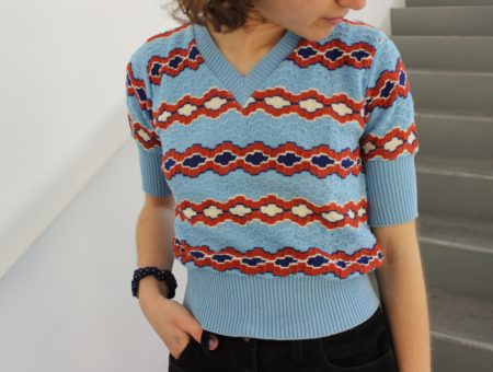This baby blue short-sleeve sweater has a rustic red and white pattern.