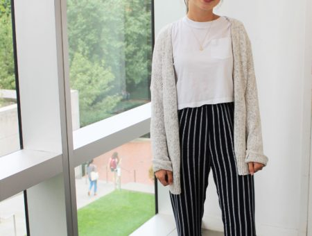 Maya, a student at Barnard College at Columbia University, sports a neutral white crop top, cozy off-white oversized cardigan, vertically striped black and white pants, and silver sandals.