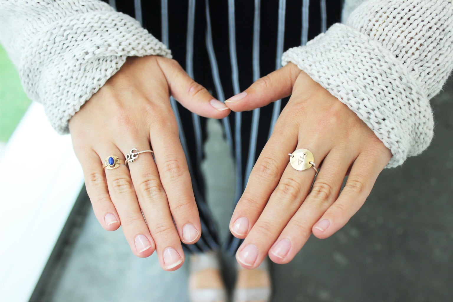 Barnard College student shows off her delicate gold rings and loose-knit white sweater.