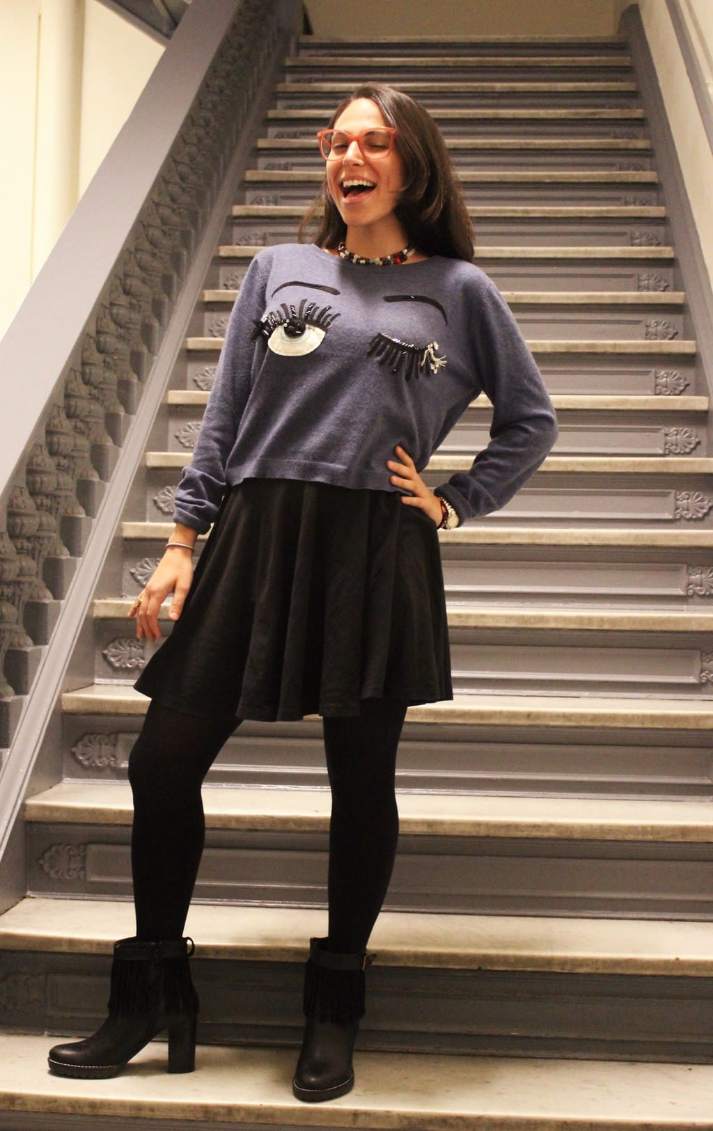 This Barnard College student wears a grey winking eye handmade grey sweater with a flowy black skirt with opaque black tights and fringe heeled black booties. She accessorizes with layered beaded necklaces and bright red eyeglasses.