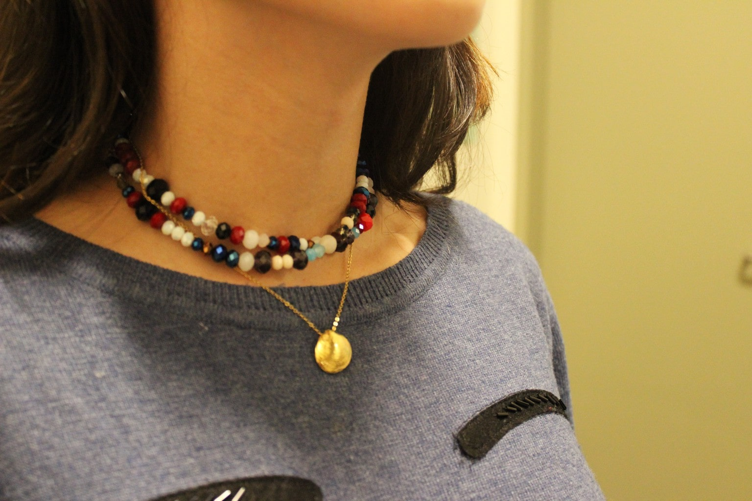 Rachel from Barnard College wears a layered beaded choker necklace with a gold pendant necklace on a delicate chain.