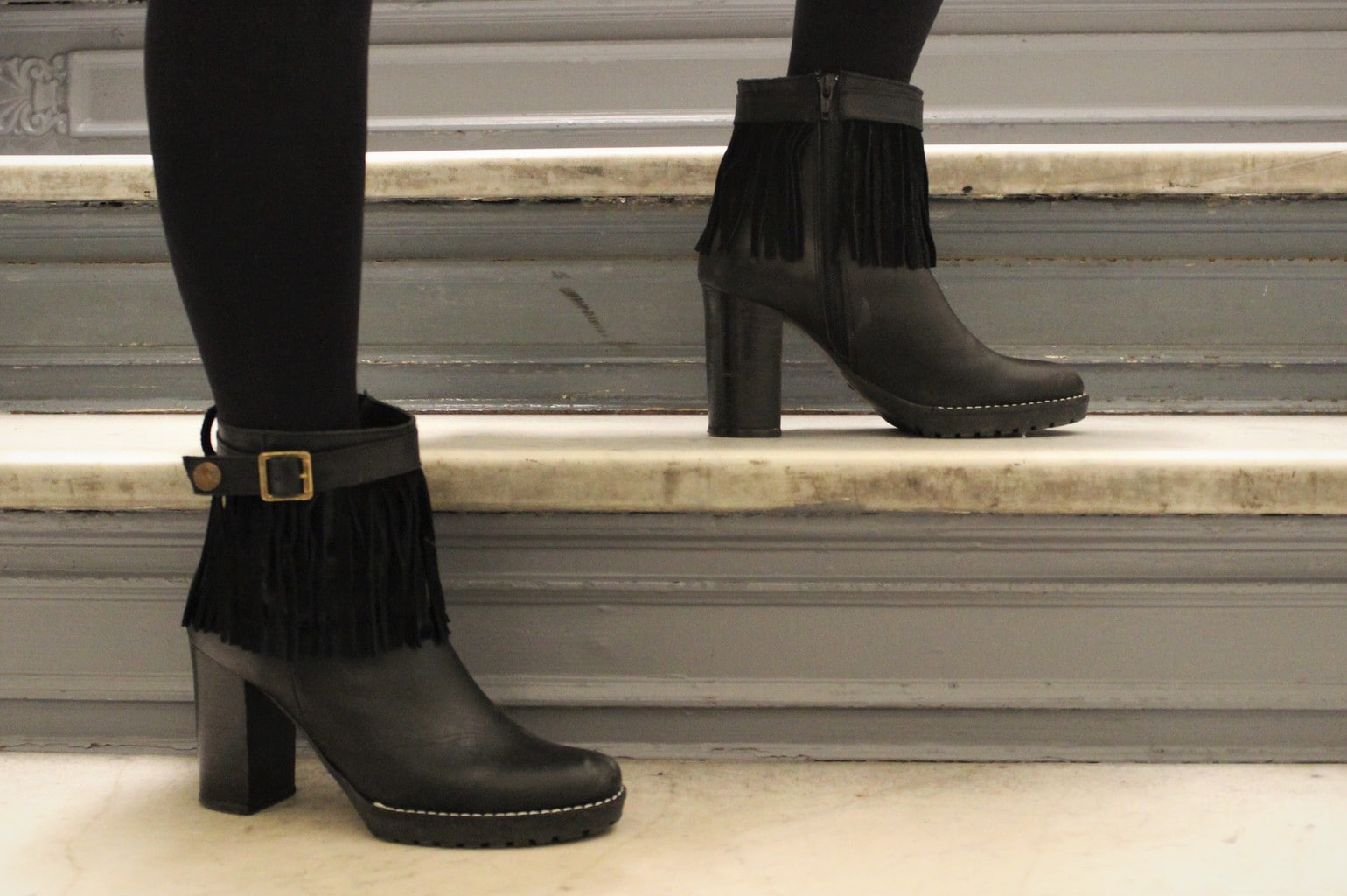 Black fringe heeled booties with gold buckles and chunky platforms.