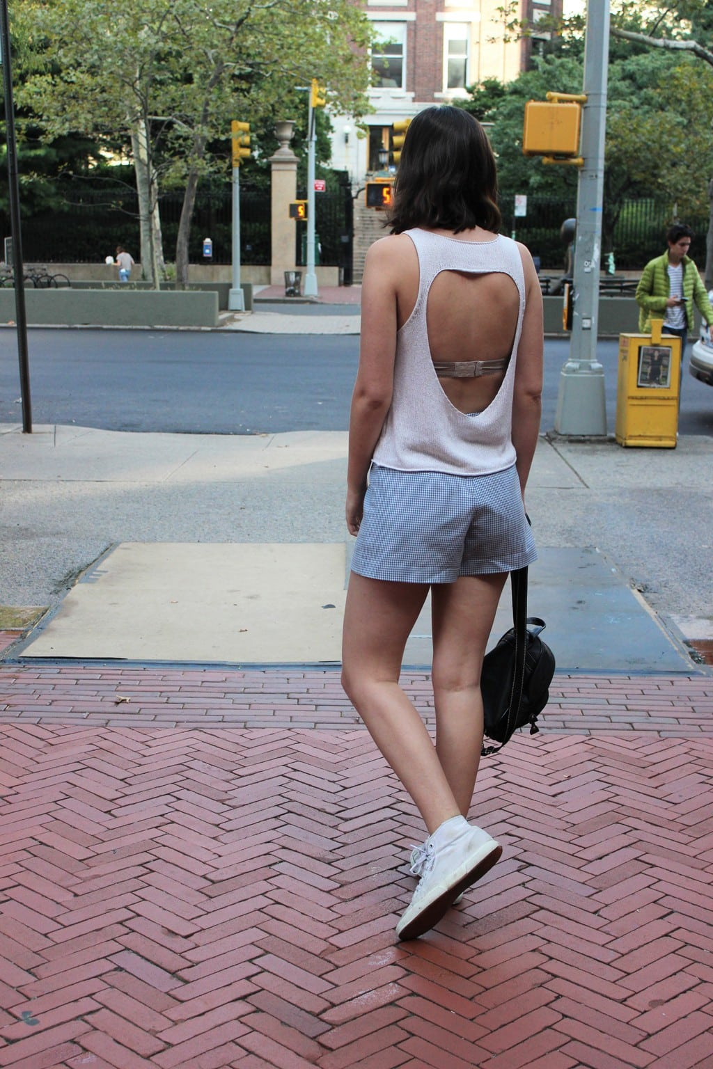 White knitted tank with open back worn with blue and white checkered gingham skort, shown as shorts from the back.
