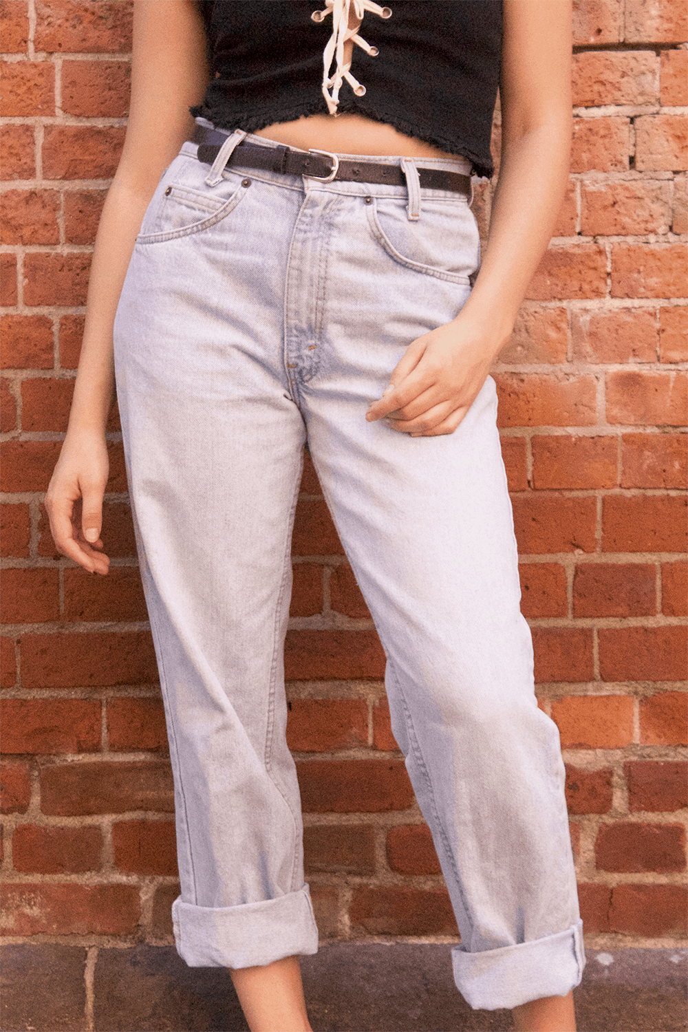 Student wears high-waisted and belted mom jeans with light wash and baggy fit.