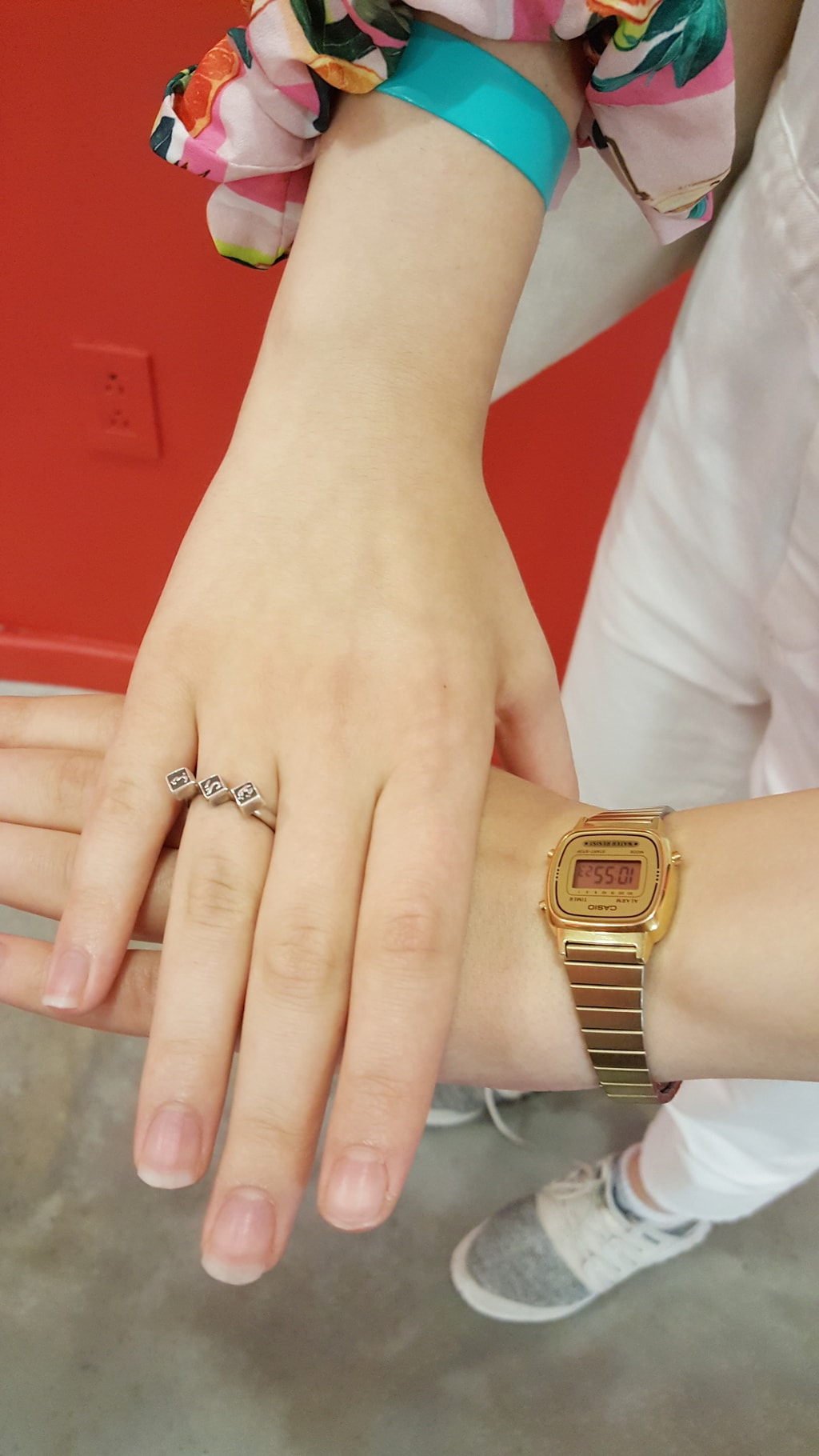 Simple gold details: a vintage gold analog watch and a delicate gold ring with three square black jewels.