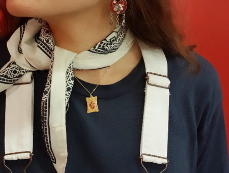A white necktie contrasts with a navy t-shirt, paired with a simple gold necklace with square pendant and red chandelier earrings.