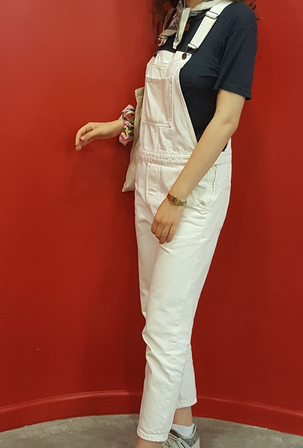 Cuffed white overalls paired with a short-sleeve navy t-shirt and a simple gold watch.