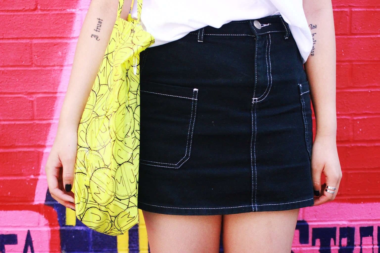 Student in NYC wears a black denim miniskirt with white stitching.