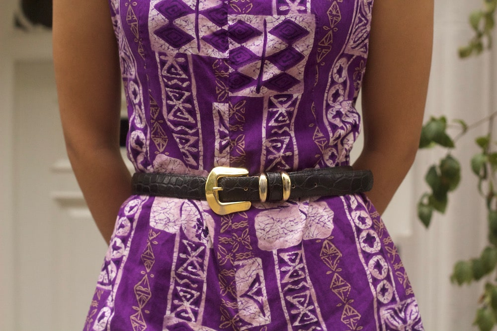 Small accents make a big impact; this brown western-style belt with shiny gold belt buckle polish off this purple romper.