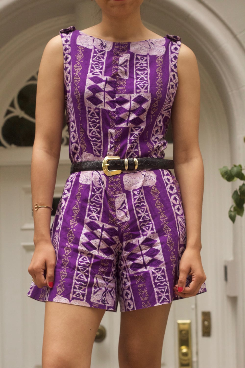This vintage thrift store purple patterned romper has buttons on the tank sleeves and has shorts, ideal for summer heat.