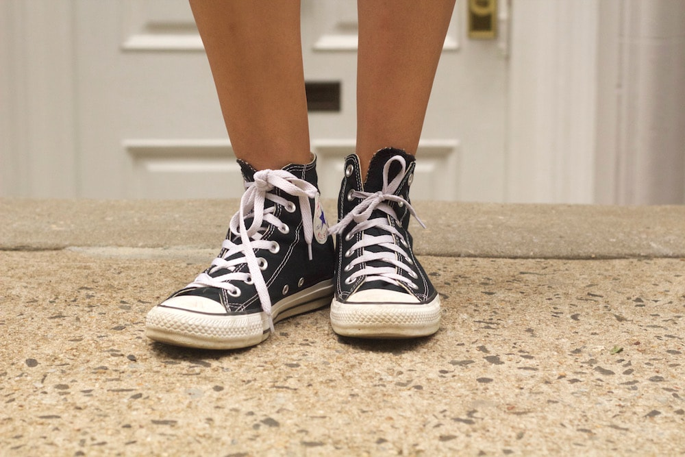 Classic black high-top Converse sneakers with bright white shoelaces.