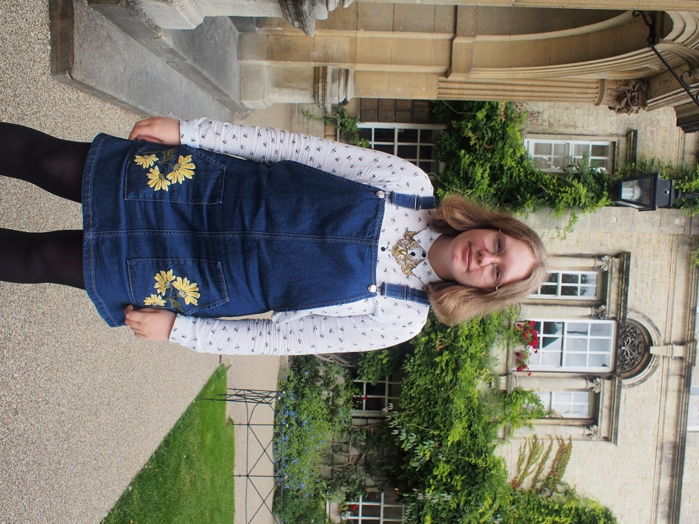 Hannah, a student at the University of Oxford, wears a denim jumper dress with yellow embroidery on the pockets, white patterned button-up with a collar, and a gold statement necklace.