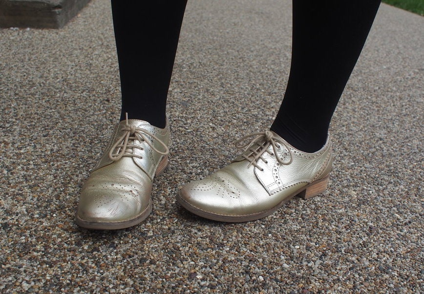 Hannah's shoes are gold lace-up oxfords which she wears with black tights.