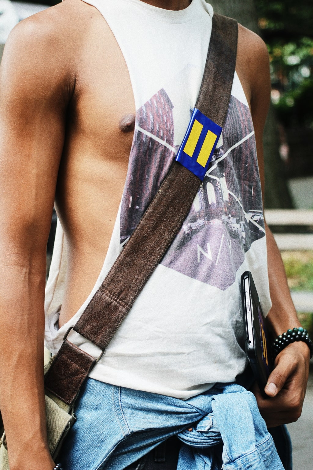 Campus trends at NYU: Student Kamron wears a muscle tank, messenger bag, and chambray shirt tied around his waist