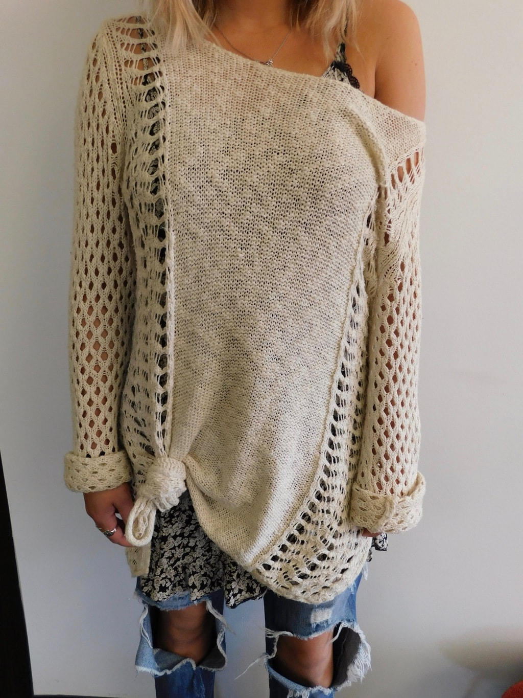 Lauren sports an oversized, casual oatmeal sweater with open weave arms and a black and white floral print camisole peeking out from underneath.