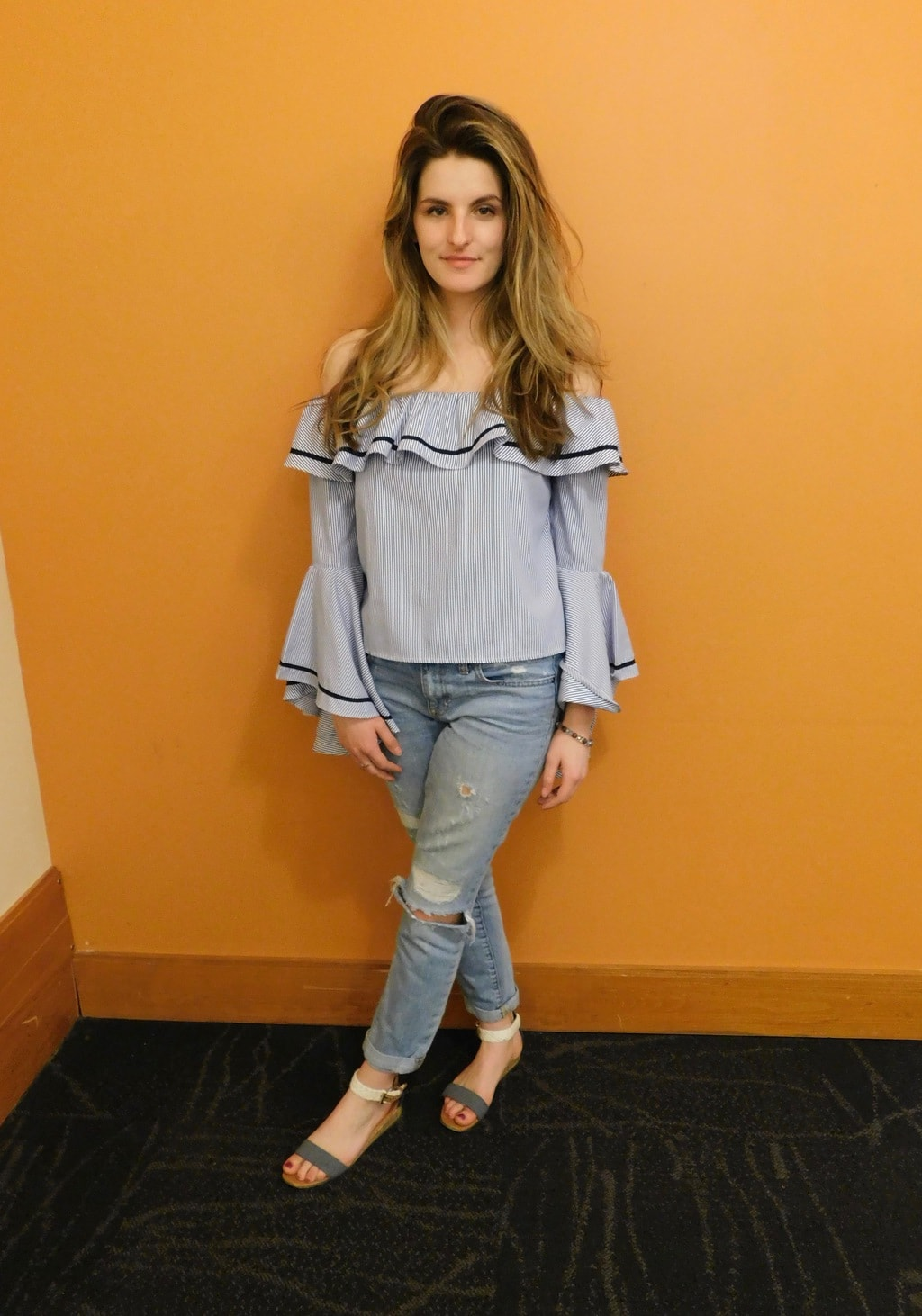 Jefferson University student Danielle wears an off-the-shoulder blue ruffled top with bell sleeves, light-wash distressed denim jeans, and simple grey and white flat sandals.
