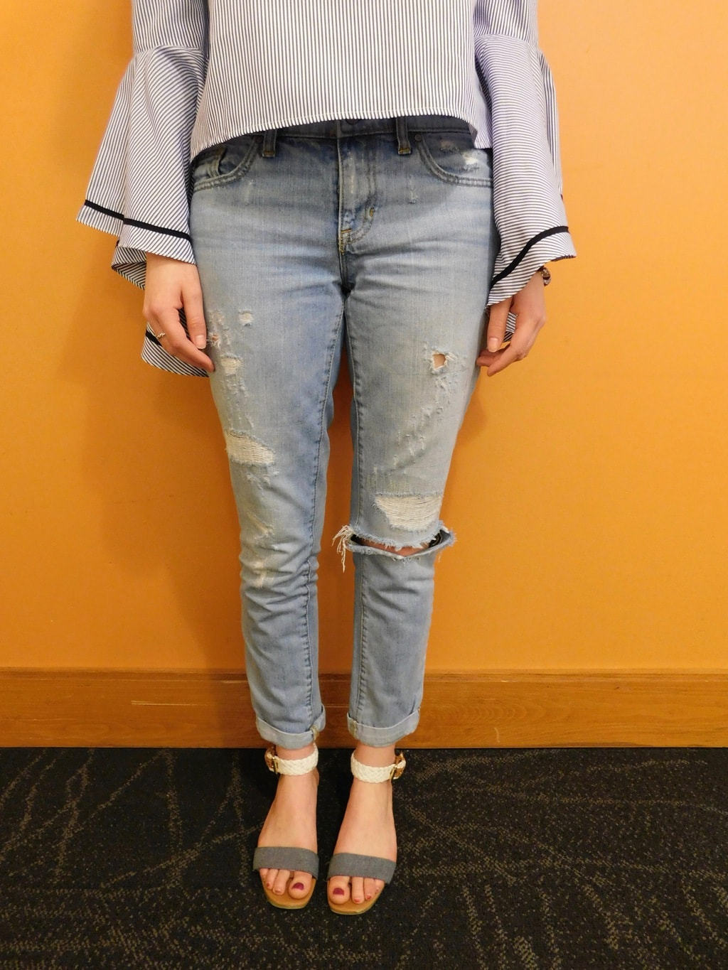Danielle wears light-wash distressed denim jeans cuffed up with white and grey flat sandals.