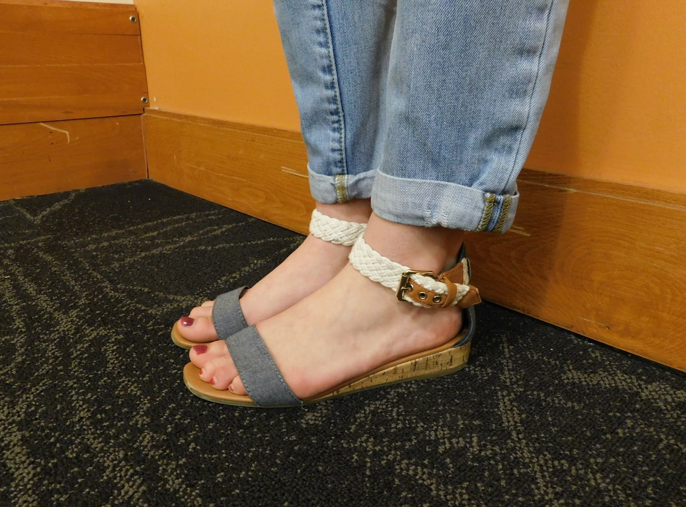 Danielle's grey denim sandals have a tiny cork wedge and a white braided ankle strap.