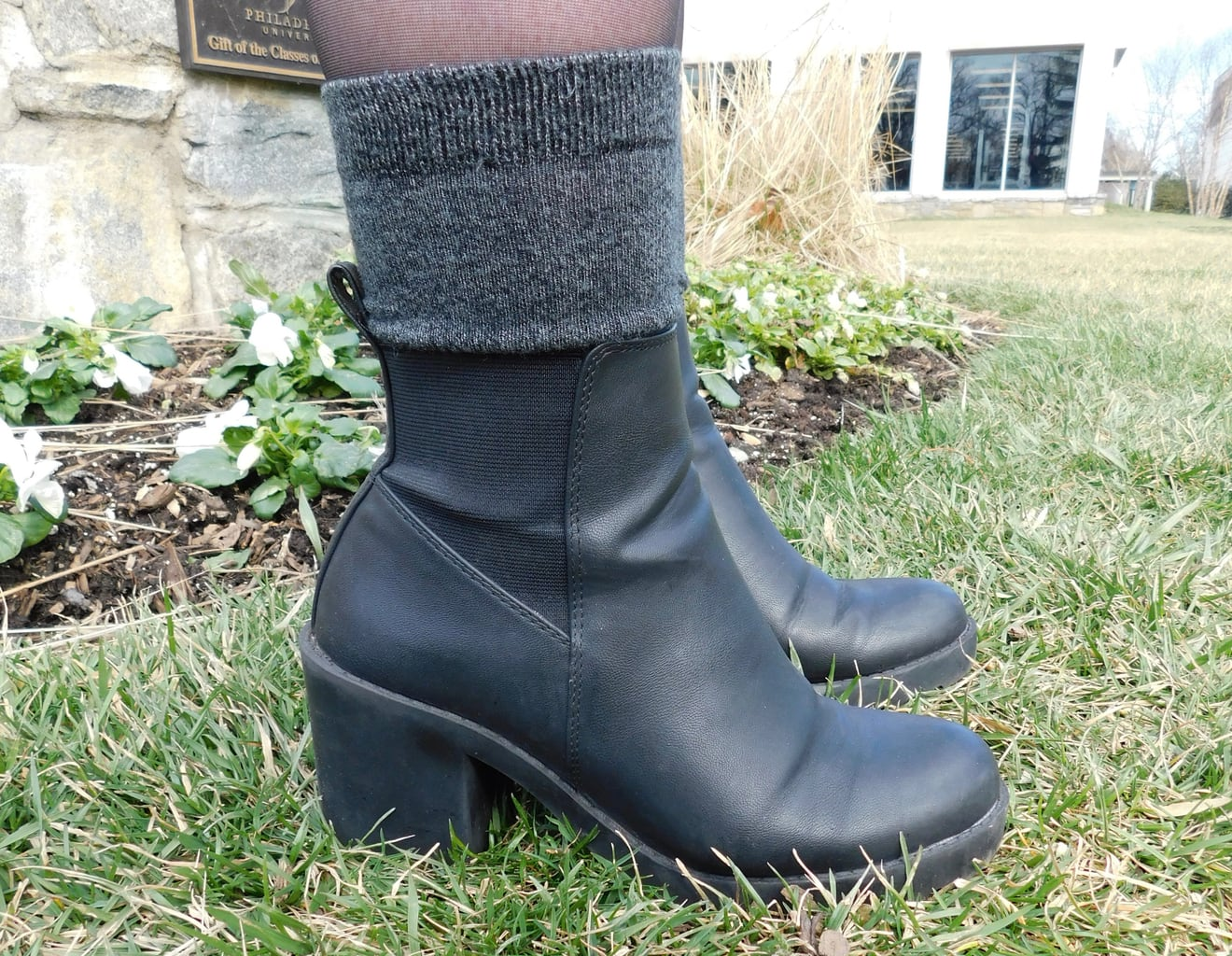 These black chunky-heeled booties with elastic detailing are accented with a pair of cozy grey boot socks.