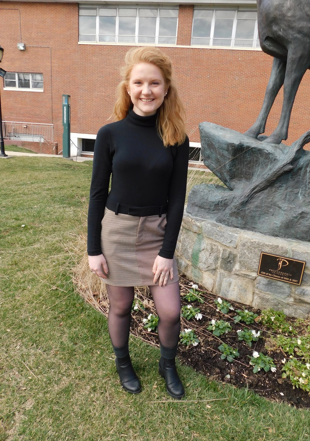 Hannah, a student a Jefferson University, wears a black long-sleeve turtleneck sweater tucked into a maroon houndstooth miniskirt with a black waistband, sheer tights, chunky black boots, and grey boot socks.