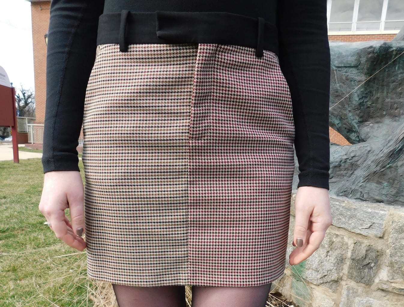 This black, white, and red houndstooth miniskirt has a black waistband.