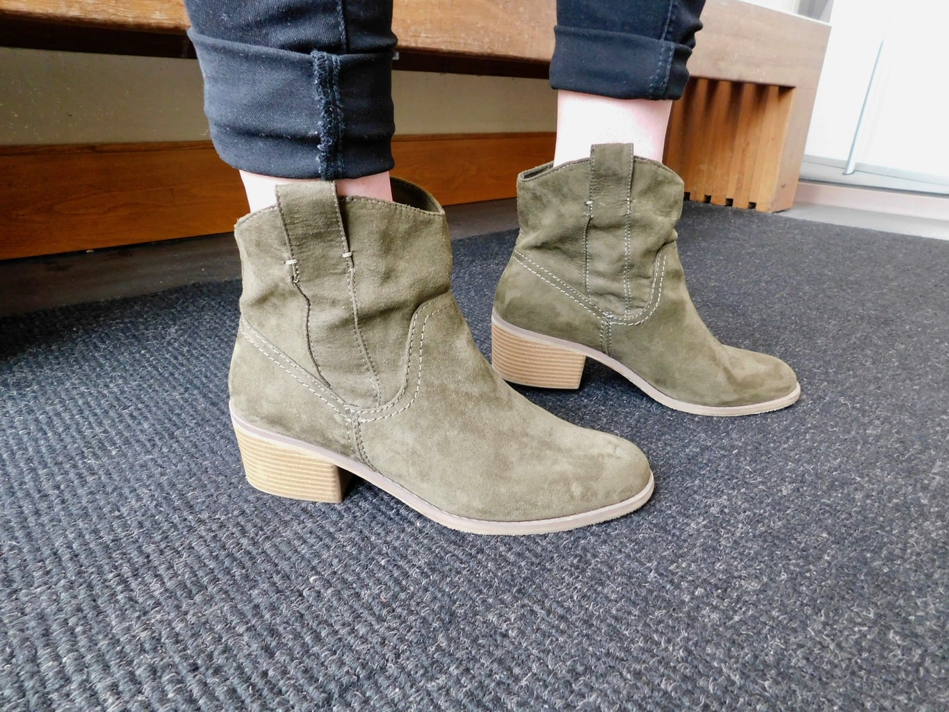 Jenna's olive green boots have a slight block heel and a Western flair.