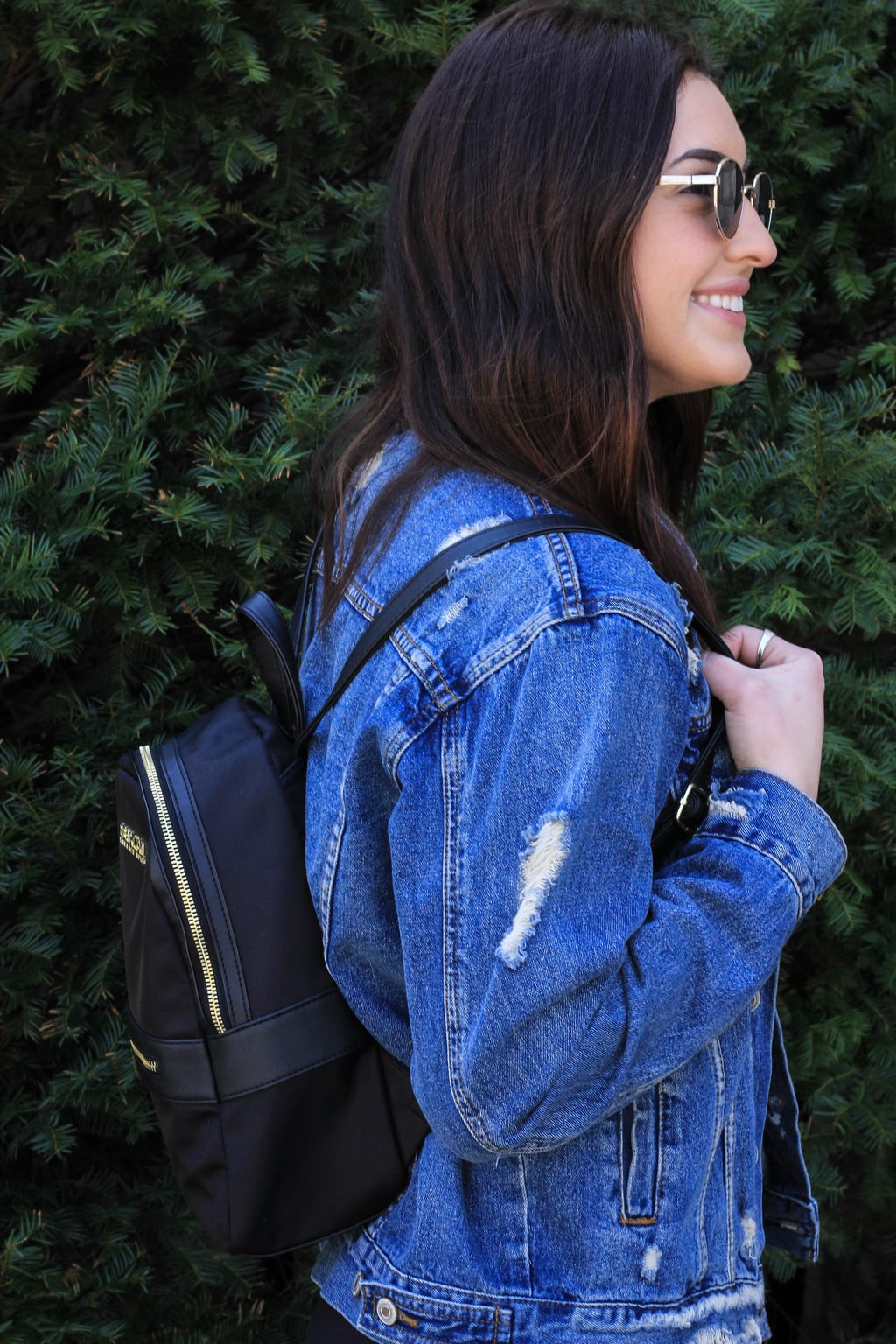 Bailey's black mini backpack with gold zippers and details carries everything she needs around campus.
